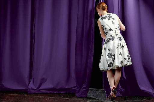 Girl looking through curtains backstage