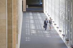 businessman and businesswoman walking in lobby of modern office