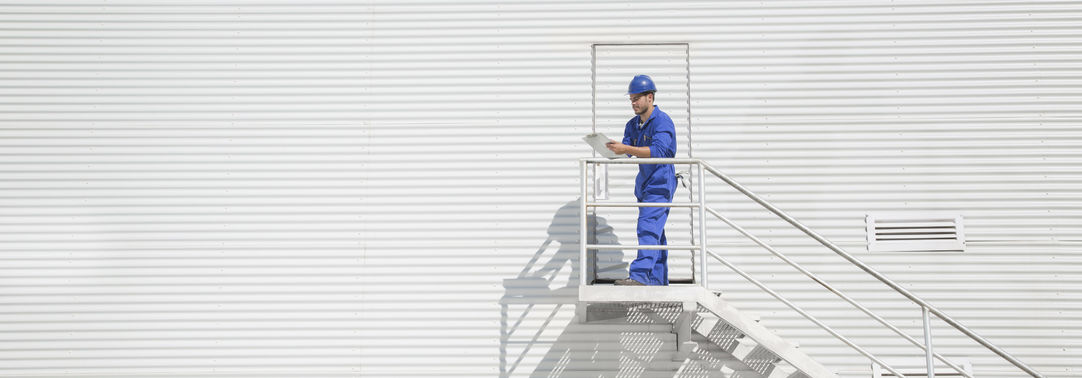 Worker with clipboard on staircase