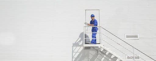 Construction worker with clipboard on staircase