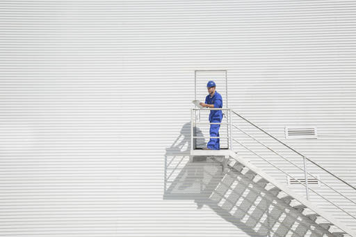 Worker with clipboard on stairs