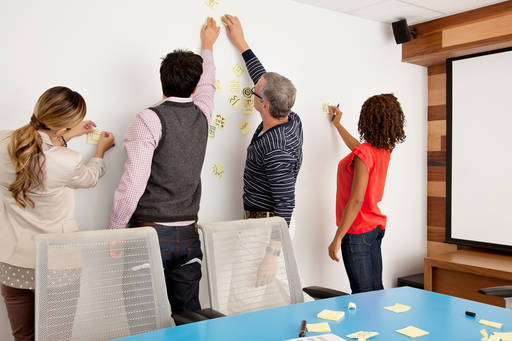 Business people putting stick notes on wall