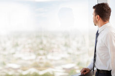 Businessman looking outside glass window