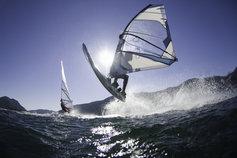 man-jumping-wave-on-windsurf-board