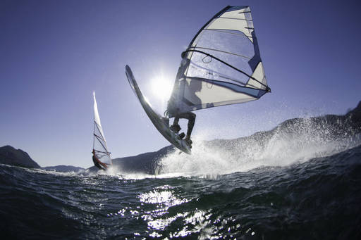 Man jumping wave on wind surf board