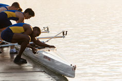 Men pulling a rowing boat along the water from the pier