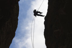 person repelling off cliff
