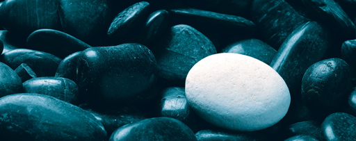 White pebble over black pebbles
