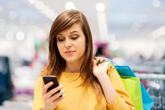 young woman texting while shopping