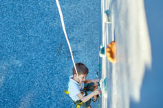 Little boy in  rock climbing gym