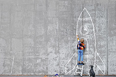 kid drawing aircraft on wall