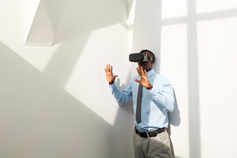 man using virtual reality glasses in white room