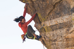 woman rock climbing up edge