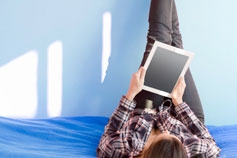 girl lying on bed with tablet and legs up
