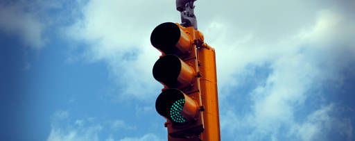 Green traffic light against a blue sky