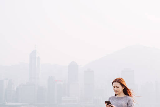 Woman looking at the screen on foggy winter morning
