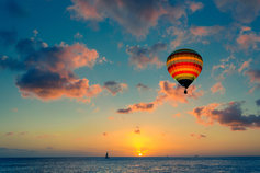Colored air balloon in clouds over sea