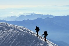 Two mountaineers walking towards summit