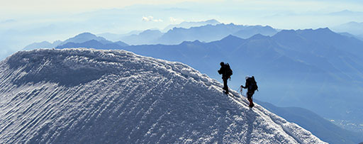 Men on mountain walking in the snow