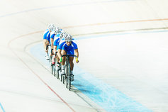 Track cyclists riding around a velodrome