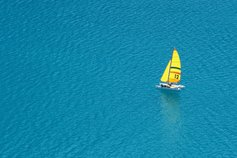 Financial instruments | A boat with a yellow sail on the open water
