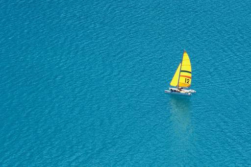 Financial instruments | Trimaran with a yellow sail on the open water