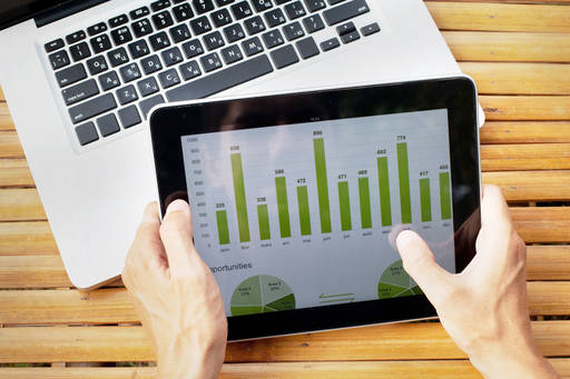 Hands of person holding tablet with green infographics on screen