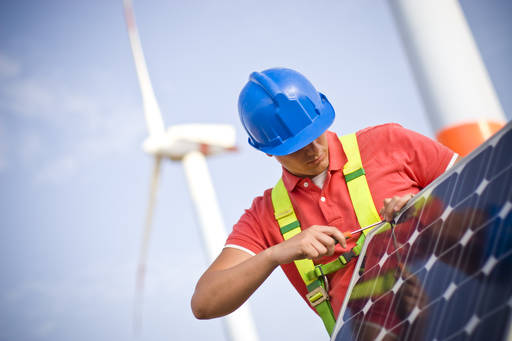 A man working on a solar panel in front of a wind turbine