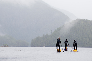 Three people paddle boarding in the rain