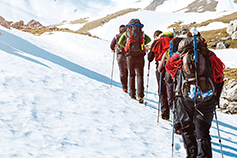 Group of people trekking on snow covered mountains