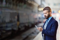 Man in train station platform looking at phone