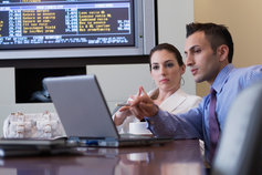 Business people discussing against web screen over laptop