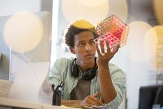 Man looking at geometric model in hand