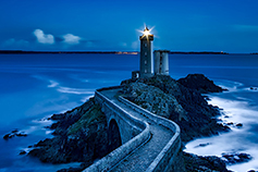 Lighthouse on the sea in the night across bridge
