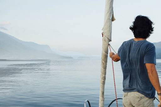 Rear view of man traveling in sailboat