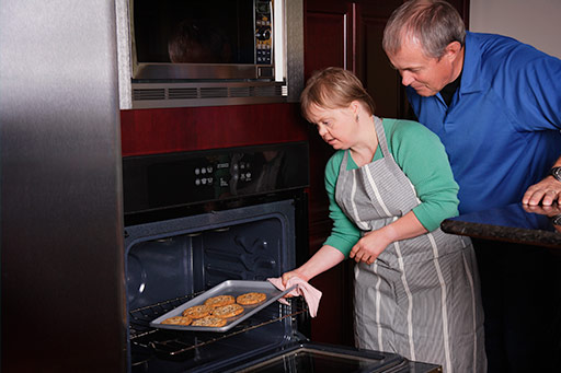 Woman with Down's Syndrome baking cookies with carer