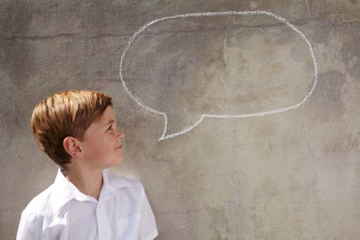 Boy looking at speech bubble on the wall