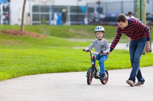 Father teaching cycling to his son in a park