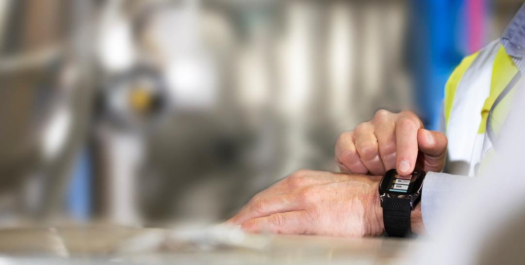 Man using smartwatch in industrial setting