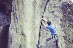 Man with blue tshirt climbing rock wall