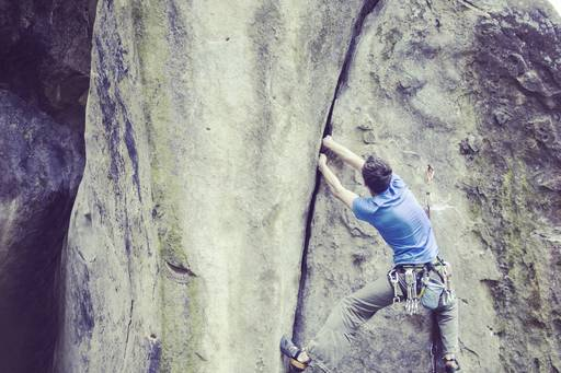 Man with blue tshirt climbing up rock wall