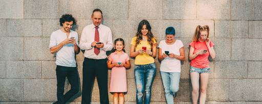 People standing against wall with phones