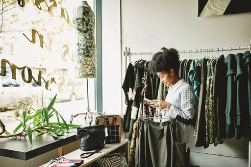 Woman in shop holding clothes and phone