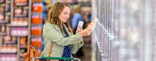 Young woman grocery shopping with phone
