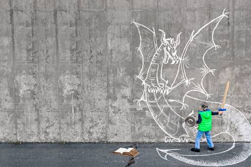 Child holding sword and facing wall where dragon is drawn with chalk , book