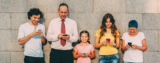 Five people standing against wall with phones in hand