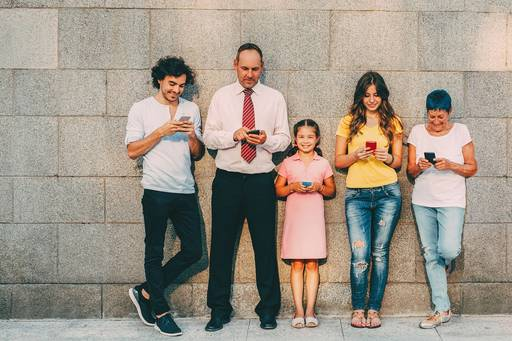 Five people standing against wall with phones in hands