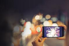 Hands holding phone and taking picture of street at night with lights in the background