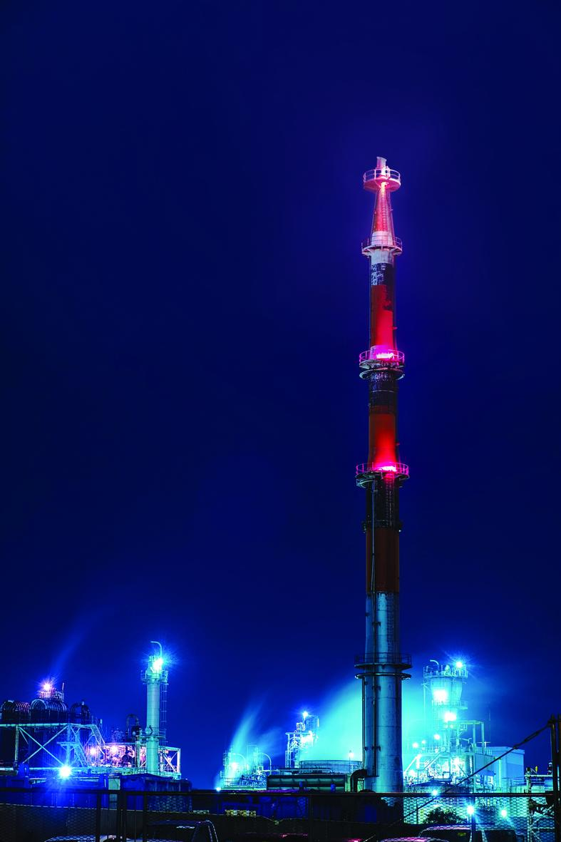 Low angle view of oil refinery tower by night