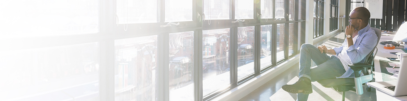Businessman looking out sunny office window